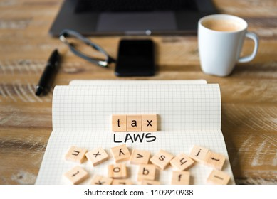 Closeup on notebook over vintage desk surface, front focus on wooden blocks with letters making Tax Laws text. Business concept image with office tools and coffee cup in background