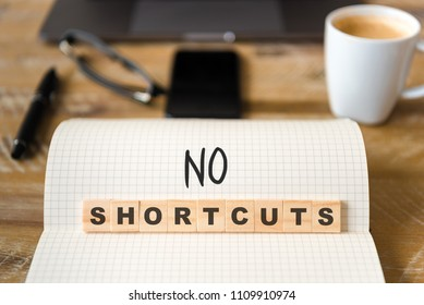 Closeup on notebook over vintage desk surface, front focus on wooden blocks with letters making No Shortcuts text. Business concept image with office tools and coffee cup in background