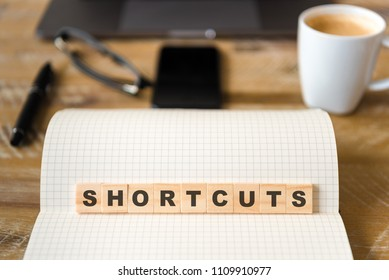 Closeup on notebook over vintage desk surface, front focus on wooden blocks with letters making Shortcuts text. Business concept image with office tools and coffee cup in background