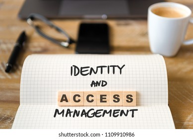 Closeup on notebook over vintage desk surface, front focus on wooden blocks with letters making Identity and Access Management. Business concept image with office tools and coffee cup in background
