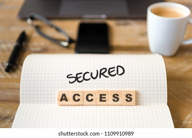 Closeup on notebook over vintage desk surface, front focus on wooden blocks with letters making g Secured Access text. Business concept image with office tools and coffee cup in background