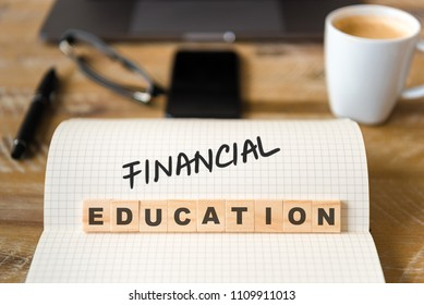 Closeup on notebook over vintage desk surface, front focus on wooden blocks with letters making Financial Education text. Business concept image with office tools and coffee cup in background