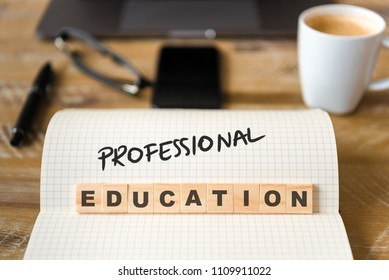 Closeup on notebook over vintage desk surface, front focus on wooden blocks with letters making Professional Education text. Business concept image with office tools and coffee cup in background