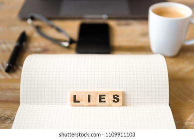 Closeup on notebook over vintage desk surface, front focus on wooden blocks with letters making Lies text. Business concept image with office tools and coffee cup in background