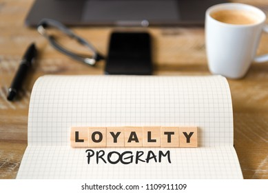 Closeup on notebook over vintage desk surface, front focus on wooden blocks with letters making Loyalty Program text. Business concept image with office tools and coffee cup in background