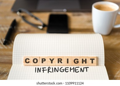 Closeup on notebook over vintage desk surface, front focus on wooden blocks with letters making Copyright Infringement text. Business concept image with office tools and coffee cup in background