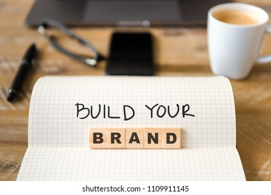 Closeup on notebook over vintage desk surface, front focus on wooden blocks with letters making Build Your Brand text. Business concept image with office tools and coffee cup in background