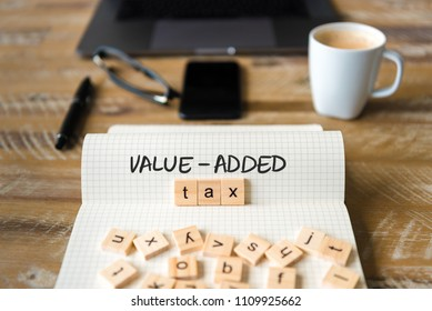 Closeup on notebook over vintage desk surface, front focus on wooden blocks with letters making Value-Added Tax VAT text. Business concept image with office tools and coffee cup in background