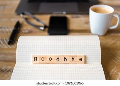 Closeup on notebook over wood table background, focus on wooden blocks with letters making Goodbye word. Business concept image. Laptop, glasses, pen and mobile phone in a defocused background.