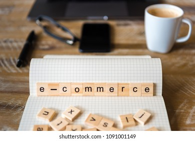 Closeup on notebook over wood table background, focus on wooden blocks with letters making Ecommerce word. Business concept image. Laptop, glasses, pen and mobile phone in a defocused background.