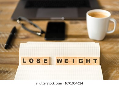 Closeup on notebook over wood table background, focus on wooden blocks with letters making LOSE WEIGHT words. Business concept image. Laptop, glasses, pen and mobile phone in a defocused background.