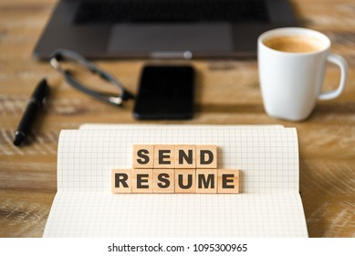 Closeup on notebook over wood table background, focus on wooden blocks with letters making SEND RESUME text. Business concept image. Laptop, glasses, pen and mobile phone in defocused background