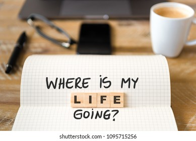 Closeup on notebook over wood table background, focus on wooden blocks with letters making Where is my life going text. Concept image with laptop, glasses, pen and mobile phone in defocused background