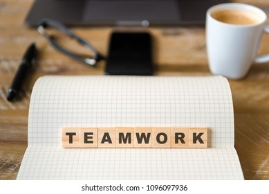 Closeup on notebook over wood table background, focus on wooden blocks with letters making TEAMWORK word. Business concept image. Laptop, glasses, pen and mobile phone in defocused background