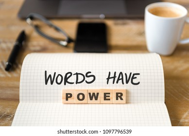 Closeup on notebook over wood table background, focus on wooden blocks with letters making WORDS HAVE POWER text. Business concept image. Laptop, glasses, pen and mobile phone in defocused background