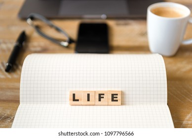 Closeup on notebook over wood table background, focus on wooden blocks with letters making LIFE word. Business concept image. Laptop, glasses, pen and mobile phone in defocused background