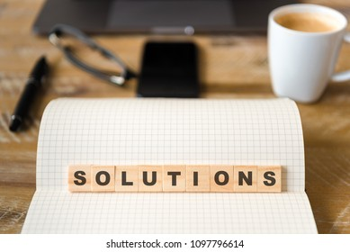 Closeup on notebook over wood table background, focus on wooden blocks with letters making Solutions word. Business concept image. Laptop, glasses, pen and mobile phone in defocused background