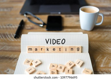 Closeup on notebook over wood table background, focus on wooden blocks with letters making Video Marketing text. Concept image with laptop, glasses, pen and mobile phone in defocused background