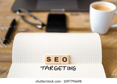Closeup on notebook over wood table background, focus on wooden blocks with letters making SEO Targeting text. Business concept image. Laptop, glasses, pen and mobile phone in defocused background