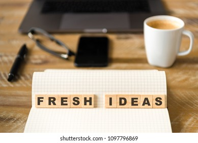 Closeup on notebook over wood table background, focus on wooden blocks with letters making Fresh Ideas text. Concept image with laptop, glasses, pen and mobile phone in defocused background