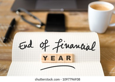 Closeup on notebook over wood table background, focus on wooden blocks with letters making End of Financial Year text. Concept image with laptop, glasses, pen and mobile phone in defocused background