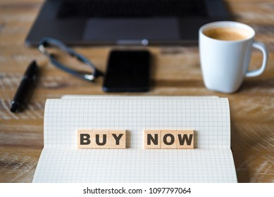 Closeup on notebook over wood table background, focus on wooden blocks with letters making Buy Now text. Concept image with laptop, glasses, pen and mobile phone in defocused background