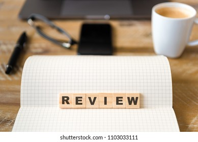 Closeup on notebook over wood table background, focus on wooden blocks with letters making Review text. Concept image. Laptop, glasses, pen and mobile phone in defocused background