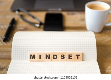 Closeup on notebook over wood table background, focus on wooden blocks with letters making Mindset text. Concept image. Laptop, glasses, pen and mobile phone in defocused background