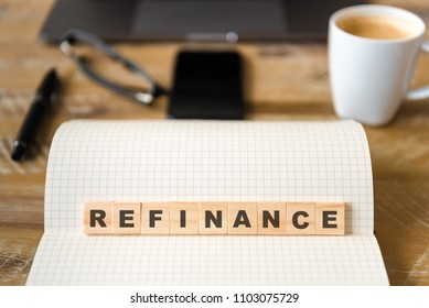 Closeup on notebook over wood table background, focus on wooden blocks with letters making Refinance text. Concept image. Laptop, glasses, pen and mobile phone in defocused background