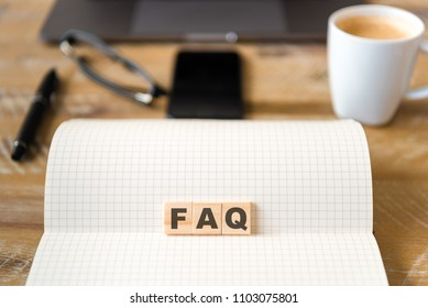 Closeup on notebook over wood table background, focus on wooden blocks with letters making FAQ text. Concept image. Laptop, glasses, pen and mobile phone in defocused background