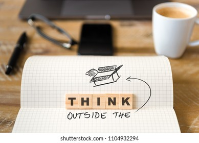 Closeup on notebook over wood table background, focus on wooden blocks with letters making Think Outside the Box text. Concept image. Laptop, glasses, pen and mobile phone in defocused background