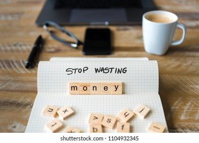 Closeup on notebook over wood table background, focus on wooden blocks with letters making Stop Wasting Money text. Concept image. Laptop, glasses, pen and mobile phone in defocused background