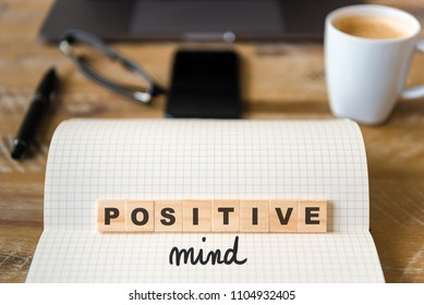 Closeup on notebook over wood table background, focus on wooden blocks with letters making Positive Mind text. Concept image. Laptop, glasses, pen and mobile phone in defocused background