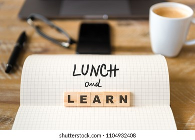 Closeup on notebook over wood table background, focus on wooden blocks with letters making Lunch and Learn text. Concept image. Laptop, glasses, pen and mobile phone in defocused background