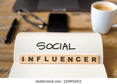 Closeup on notebook over wood table background, focus on wooden blocks with letters making Social Influencer text. Concept image. Laptop, glasses, pen and mobile phone in defocused background
