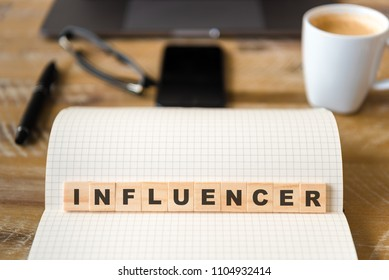 Closeup on notebook over wood table background, focus on wooden blocks with letters making Influencer text. Concept image. Laptop, glasses, pen and mobile phone in defocused background