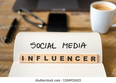 Closeup on notebook over wood table background, focus on wooden blocks with letters making Social Media Influencer text. Concept image. Laptop, glasses, pen and mobile phone in defocused background