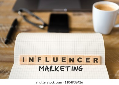 Closeup on notebook over wood table background, focus on wooden blocks with letters making Influencer Marketing text. Concept image. Laptop, glasses, pen and mobile phone in defocused background