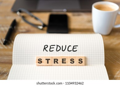 Closeup on notebook over wood table background, focus on wooden blocks with letters making Reduce Stress text. Concept image. Laptop, glasses, pen and mobile phone in defocused background