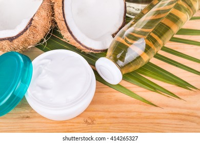 Closeup on old pressed extra virgin coconut oil in bottles and coconut processed oil in skincare jars with coconut fruits as background