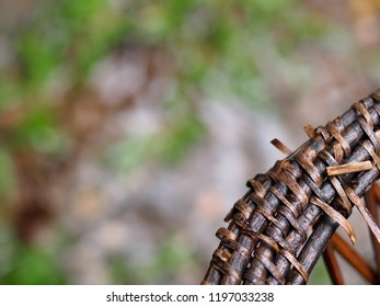 closeup on old weathered defect crafts product from woven bamboo in a contemporary asian traditional household style handmade weaving bamboo with blur green background for sustainable design concept
