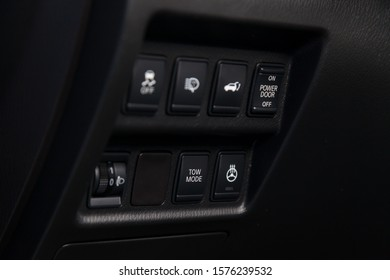 Close-up on a part of the interior of a modern luxury car with a view of the heated steering wheel, trunk open, stability system buttons with black trim elements