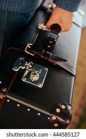 Closeup on person hand holding beautiful vintage suitcase over luxury interior background
