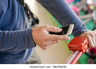 Closeup on person holding mobile smart phone in hand during shopping. Cellphone and cart on store goods background