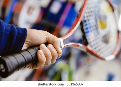 Closeup on person holding tennis racket in his hand on shopping centre background