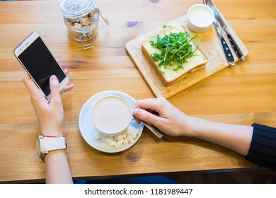 Closeup on person sitting in cafe having ice cream and coffee, working on mobile phone. Mockup top view table background