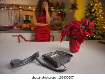 Closeup on phone on kitchen desk and stressed woman in background