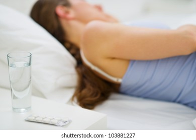Closeup on pills and glass of water on table and sleeping girl in background