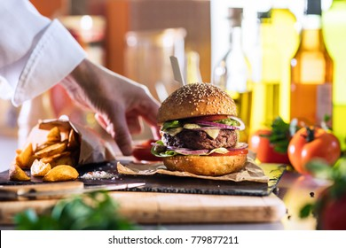 close-up on the preparation of a magnificent burger in a restaurant, the chef places a cup of ketchup near the potatoes.