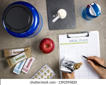 Closeup on protein jar, shaker, measuring spoon, raw protein bars, red apple, sport supplements in tablets laying on floor and female hand with pen filling meal plan and holding fitness energy bar.